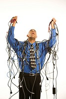 Businessman holding tangled cords