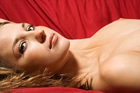 Sexy nude Caucasian young adult female lying seductively on red background looking at viewer
