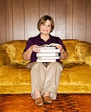 Caucasian middle aged woman sitting on couch in living room holding stack of books