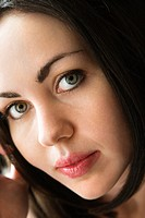 Close up of Caucasian young adult woman looking at viewer.