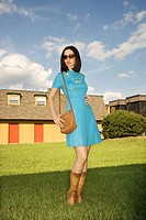 Young adult Caucasian woman in retro dress posing outdoors