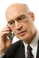 Caucasian middle_aged businessman talking on cellphone against white background