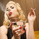 Attractive Caucasian woman holding a martini and smoking a cigarette