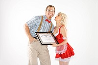 Man dressed like nerd receiving kiss and certificate from woman dressed in french maid outfit