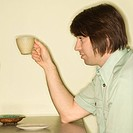 Side view of Caucasian mid_adult man holding up coffee cup