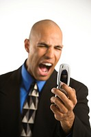 Head and shoulder portrait of African American man in suit yelling at cellphone