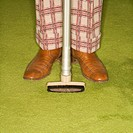 Close_up of Caucasian male legs in plaid pants with vacuum extension standing on green retro carpet
