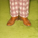 Close_up of Caucasian male legs in plaid pants standing on green retro carpet