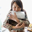 Pretty young Asian woman holding typewriter and biting page