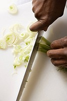 African_American male hands using large kitchen knife to chop fennel