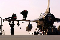 Crew chiefs prepare an F_16 Fighting Falcon for take off