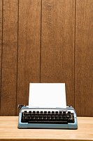 Vintage blue typewriter on desk with wood paneling