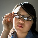 Head and shoulder portrait of pretty young Asian woman wearing eyeglasses