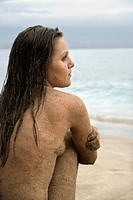 Side view of Caucasian young adult nude woman sitting on beach