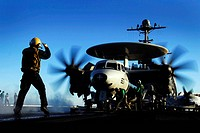 An aircraft flight deck director guides an E_2C Hawkeye onto a steam propelled catapult for launch off the flight deck