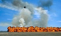 Pyrotechnics explode while an F_15 flies over to simulate an air_to_ground attack