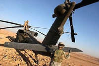 Soldiers prepare a UH_60 Black Hawk Helicopter to be transported after hitting a land mine