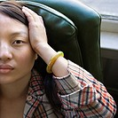 Pretty young Asian woman sitting in green chair with hands on her head