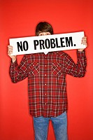 Portrait of Caucasian teen boy holding no problem sign under his eyes