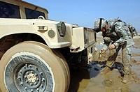 Staff Sergeant unties a rope to tow a humvee out of the mud