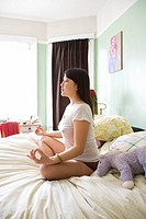 Side view of pretty Asian young woman sitting on bed in underwear and t_shirt meditating in lotus pose