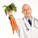 Caucasian mid adult male physician holding bunch of carrots