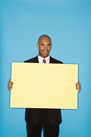 African American man holding blank sign against blue background