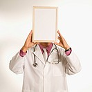 Asian American male doctor holding blank sign over face