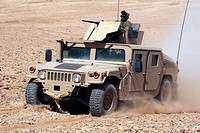 Humvee cruises up a dusty slope during a perimeter patrol