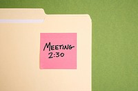 Folder with pink sticky note reminder for a meeting on a green background