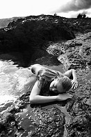 Young nude woman partially submerged in water laying face down on rocky coast