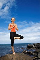 Caucasian young adult woman doing yoga on rocky shore