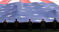 Airmen present a 100_yard_by_50_yard American Flag during the National Anthem