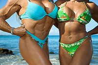 Close up torsos of Caucasian mid adult women bodybuilders in bikinis standing on beach