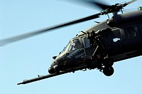 An aerial gunner waves goodbye from the HH_60G Pave Hawk as it flies away