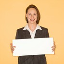 Businesswoman smiling holding blank sign