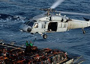 U.S. Navy Sailors attach pallets of supplies to an MH_60S Knighthawk helicopter