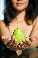 Woman holding pear in outstretched hands toward viewer