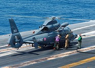 Sailor refuels a French Dauphin 35F helicopter on the flight deck