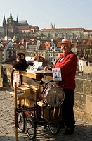 Czech Republic. Prague. Musician at Charles´ brigde. Old town and castle in the backround.