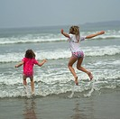 Two girls jumping in water on beach