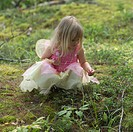 Young girl in a fairy costume squatting in the grass