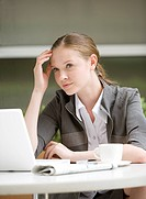 Close_up of businesswoman using laptop and looking away