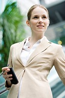 Close_up of businesswoman holding PDA and looking away
