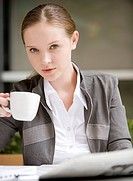 Close_up of businesswoman holding coffee cup and looking at the camera