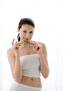 Close_up of young woman holding herbs and looking at the camera