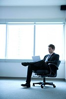 Businessman using laptop on chair, side view