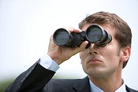 Businessman using binoculars, close_up