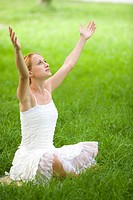 Young woman sitting on grass with arms raised