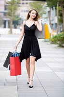 Teenage girl holding shopping bags walking on street
